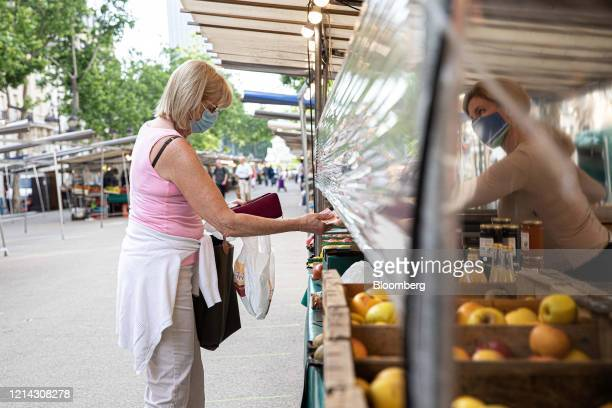 A customer wearing a protective face mask hands euro banknotes under a protective cellophane screen on a fruit and vegetable stall at Marche...