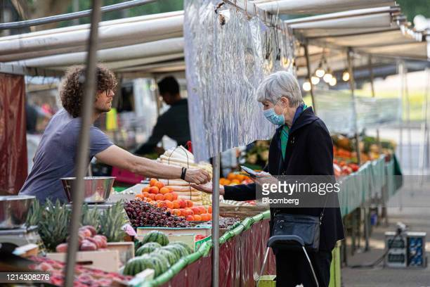 A customer wearing a protective face mask is handed their change under a protective cellophane screen on a fruit and vegetable stall at Marche...