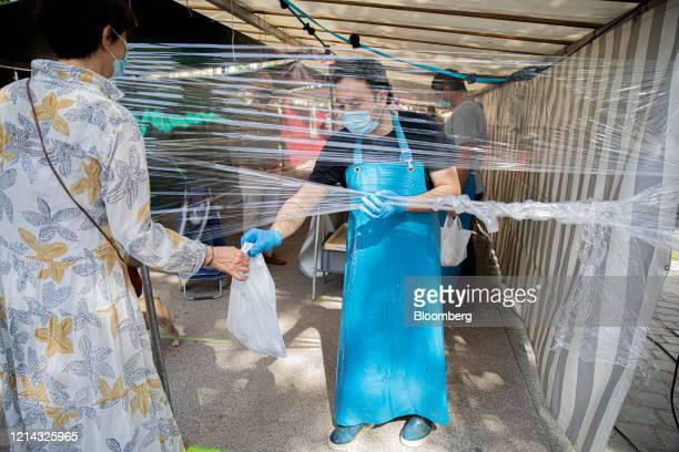 A customer wearing a protective face mask is handed their purchase under a protective cellophane screen on a fruit and vegetable market stall at...