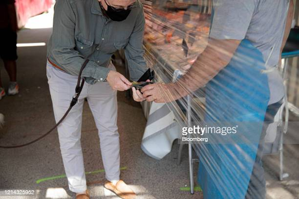 A customer wearing a protective face mask makes a card payment transaction under a protective cellophane screened market stall at Marche SaxeBreteuil...