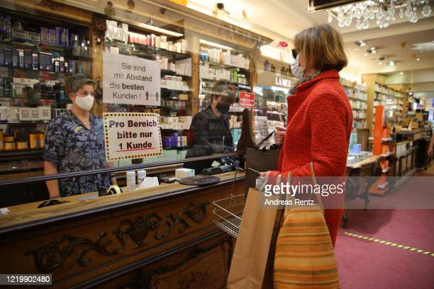 Customer wearing a protective face mask pays for her purchase at the checkout with a protective plexiglass stand at a re-opened perfumery shop on the...