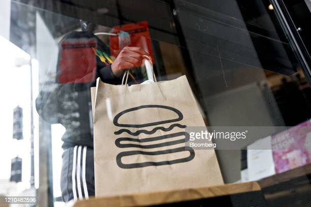 Customer wearing a protective mask picks up a take-out order at a Shake Shack restaurant in Washington, D.C., U.S., on Monday, April 20, 2020. Shake...