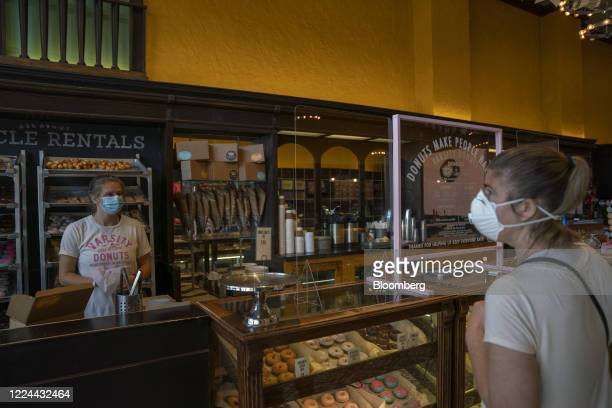 Customer wearing a protective mask places an order at a donut shop in Manhattan, Kansas, U.S., on Thursday, July 2, 2020. Kansas' top public health...