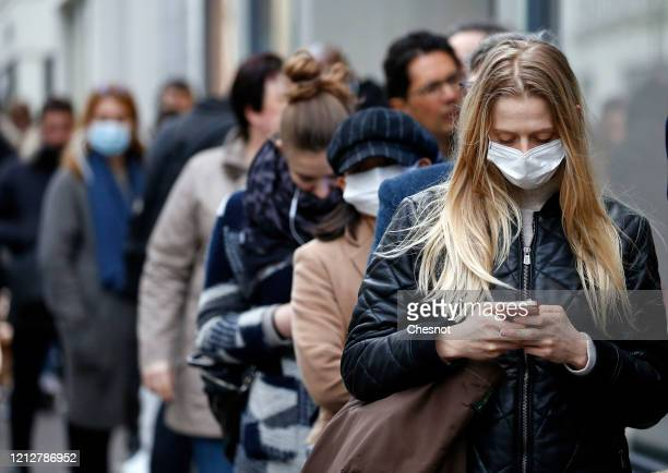 A customer wearing a protective mask queues in front of a Monoprix supermarket as people began stockpiling food in Paris due to an outbreak of...