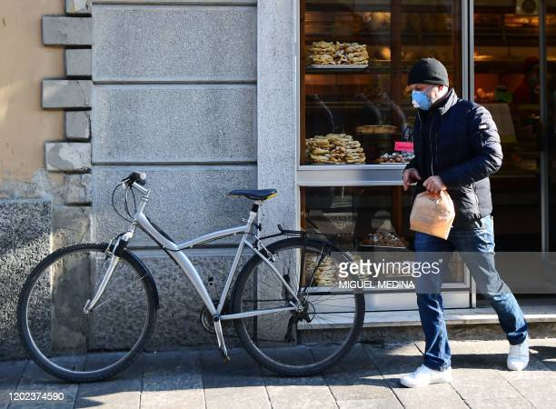 Customer wearing a protective respiratory mask leaves a bakery in Codogno, southeast of Milan, on February 22, 2020. - An Italian man became the...