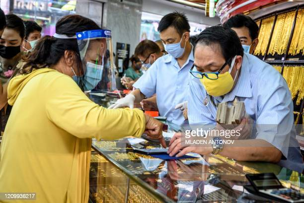 A customer wearing a protective shield and a facemask amid fears of the spread of COVID19 coronavirus sells her jewelries in a gold shop in Bangkok's...