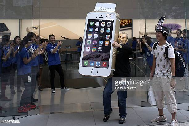A customer wearing a Steve Jobs mask celebrates after purchasing a new iPhone at the launch of the new Apple iPhone 6 and iphone 6 plus at the Apple...