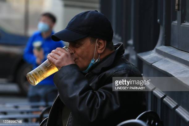 Customer, wearing his face mask or covering pulled under his chin, drink a pint of beer as he sit at a table outside a pub in Liverpool, north west...