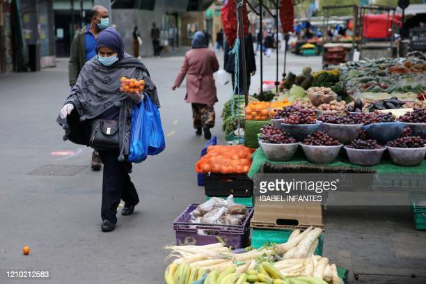 Customer wearing PPE of a face mask as a precautionary measure against COVID-19, walks with a punnet of tangerines after buying them from a market...