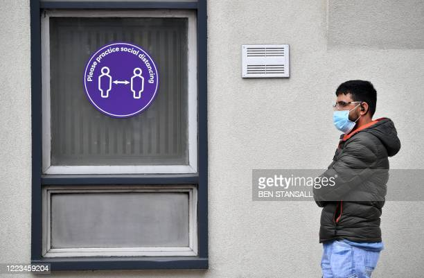 Customer wearing PPE , of a face mask or covering as a precautionary measure against spreading COVID-19, stands near a sign asking people to socially...