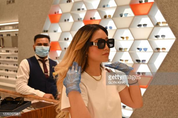 Customer wearing protective gloves tries on sunglasses as a member of staff looks inside Selfridges department store on Oxford Street in London on...