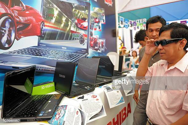 A customer wears 3D glasses as he views a 3D movie on a Toshiba computer during an exhibition in Phnom Penh on September 11 2010 Cambodia lauched the...