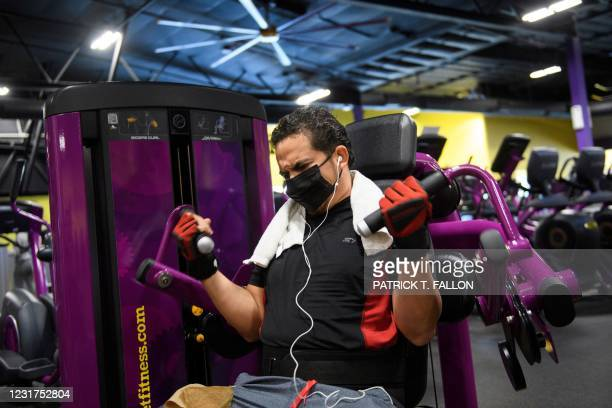 Customer wears a face mask as they lift weights while working out inside a Planet Fitness Inc. Gym as the location reopens after being closed due to...