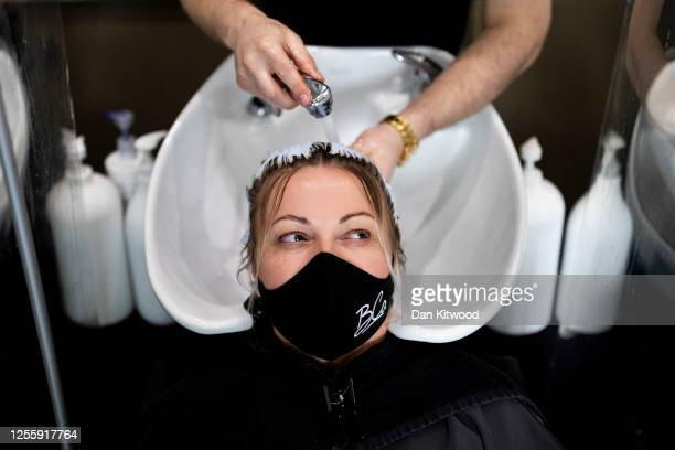 Customer wears a face mask while having her hair washed at a salon in Marylebone on July 13, 2020 in London, England. Nail salons, tattoo parlors and...