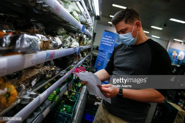 Customer wears a face mask while shopping at a M&S in Islington on July 11, 2020 in London, England. On Friday, Scotland made it mandatory to wear...