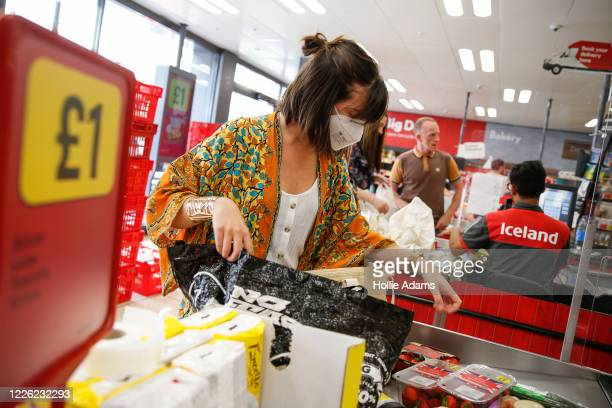 Customer wears a face mask while shopping at Iceland in Islington on July 11, 2020 in London, England. On Friday, Scotland made it mandatory to wear...
