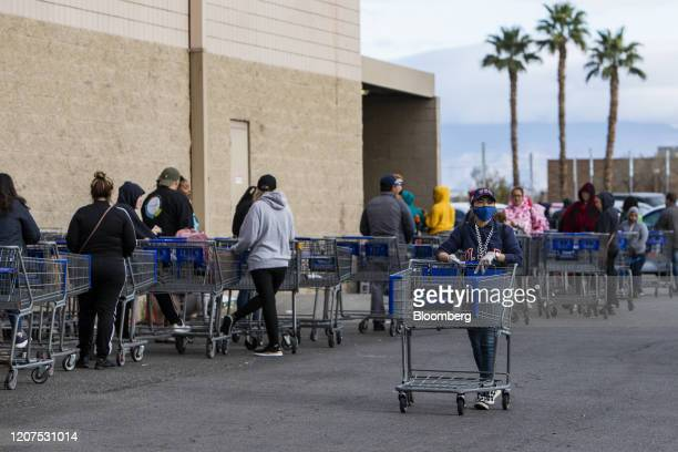 Customer wears a protective mask while pushing a shopping cart outside a Sam's Club ahead of opening hours in Las Vegas, Nevada on Tuesday, March 17,...