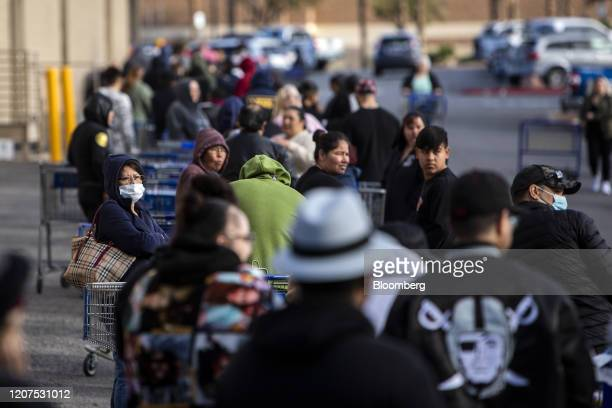 Customer wears a protective mask while standing in line outside a Sam's Club ahead of opening hours in Las Vegas, Nevada on Tuesday, March 17, 2020....