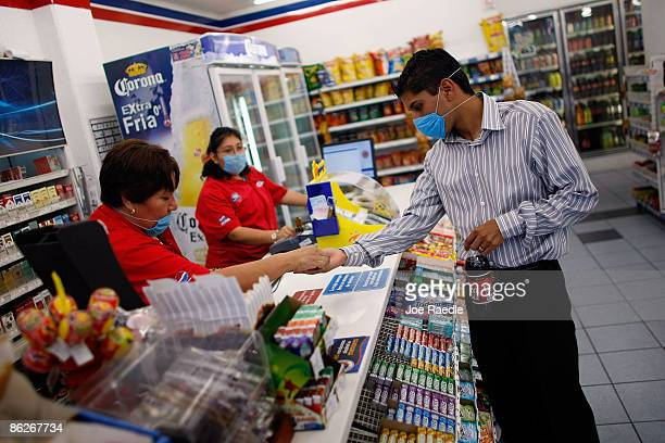 A customer wears a surgical mask to help prevent being infected with the swine flu as he buys a soda on April 28 2009 in Mexico City Mexico Reports...
