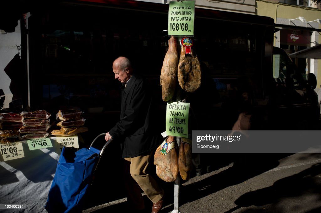 A customer wheels a shopping cart past legs of Iberico ham hanging outside a store at the weekly market in Figueres, Spain, on Thursday, Jan. 31, 2013. Spain's recession deepened more than economists forecast in the fourth quarter as the government's struggle to rein in the euro region's second-largest budget deficit weighed on domestic demand. Photographer: David Ramos/Bloomberg via Getty Images