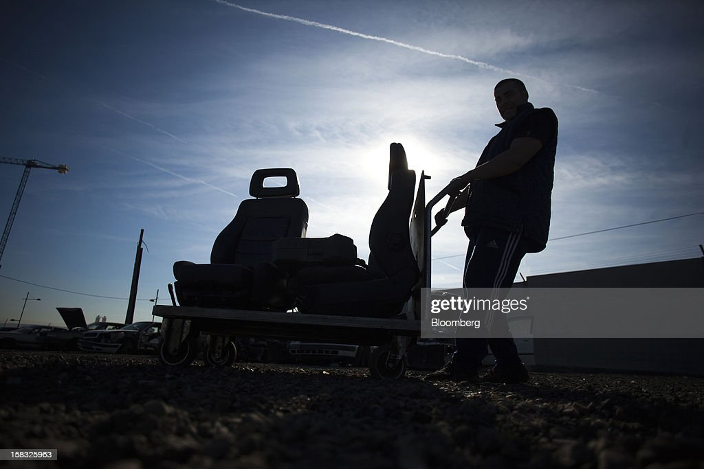 A customer wheels a trolley with two car seats sourced from scrapped automobiles in the yard of the Desguaces La Torre scrapyard in Madrid, Spain, on Thursday, Dec. 13, 2012. Spain has completed the debt sales it planned for this year and started raising funds for 2013, buying time for Prime Minister Mariano Rajoy as he decides whether to seek a European bailout. Photographer: Angel Navarrete/Bloomberg via Getty Images