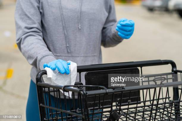 customer wipes down handles of grocery cart - disinfection stock pictures, royalty-free photos & images