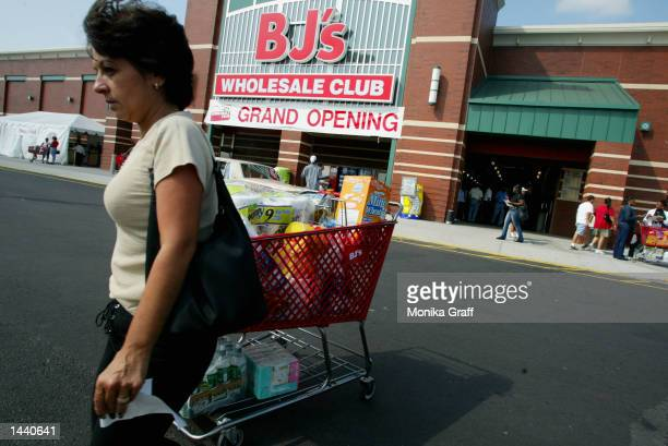 A customer with a loaded cart heads for her car after shopping at BJ's Warehouse October 1 2002 at the Gateway Center in Brooklyn New York during the...