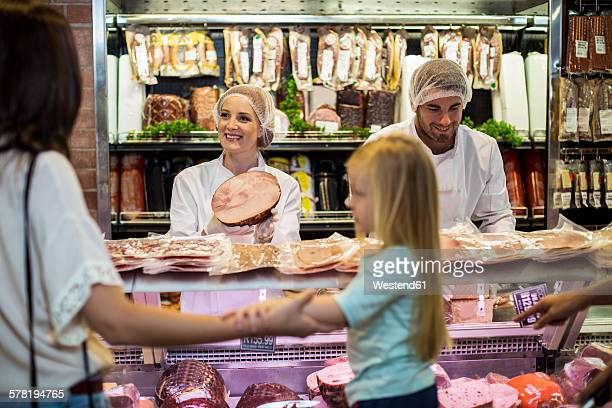 Customer with daughter buying ham at butchery
