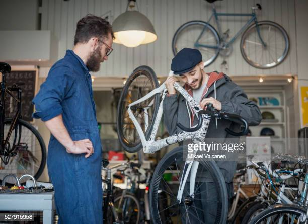 customer with mechanic looking at ultra light bicycle in bike shop
