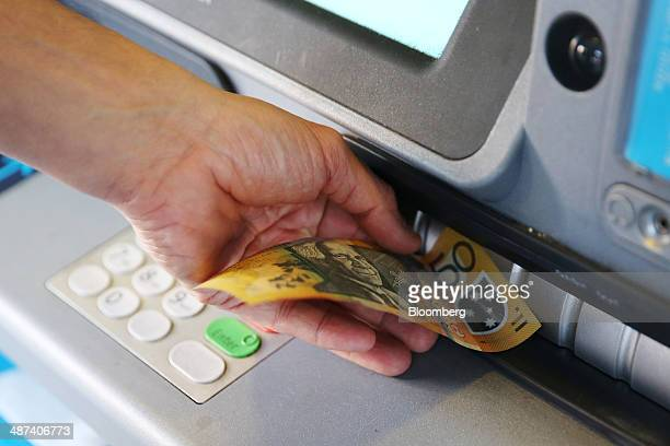 A customer withdraws a 50 Australian dollar banknote from an Australia New Zealand Banking Group Ltd automated teller machine in Sydney Australia on...