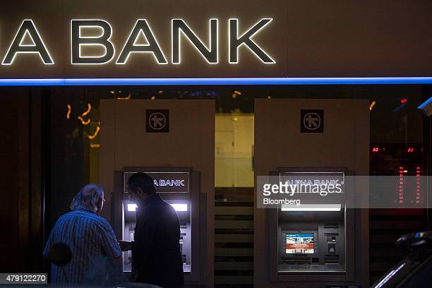 A customer withdraws cash from an automated teller machine outside a closed Alpha Bank AE bank branch illuminated at night in Athens Greece on...