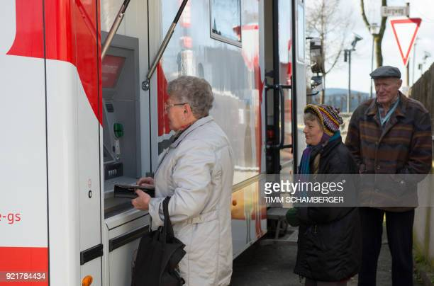 A customer withdraws money from a cash machine at a mobile office bus of the savings bank Sparkasse in Tschirn southern Germany on January 30 2018...