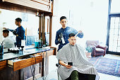 customer working smartphone while having hair