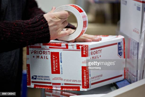 A customer wraps a United States Postal Service priority mail package with tape at the USPS Suburban post office station in Gaithersburg Maryland US...