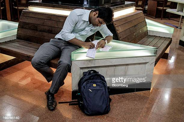 A customer writes on a cheque deposit slip at a HDFC Bank Ltd bank branch in Mumbai India on Friday Feb 1 2013 HDFC Bank India's secondlargest lender...