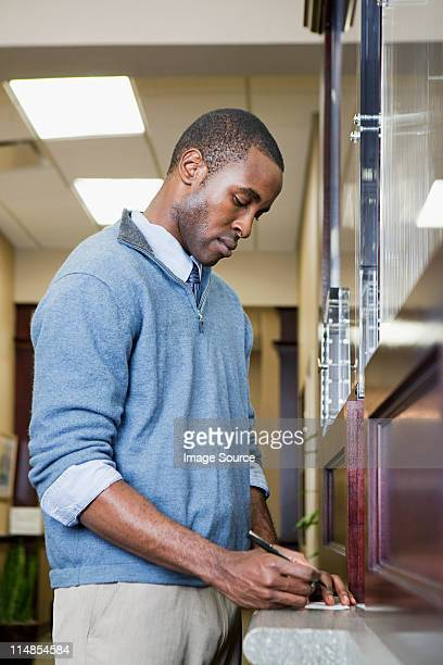 Customer writing cheque at bank counter