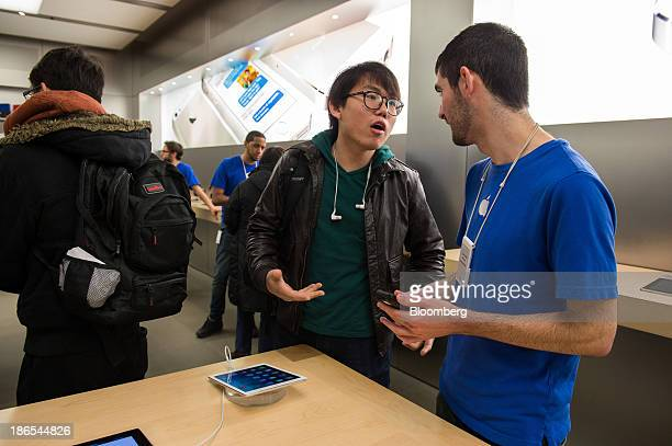 Customer Yi Zhangof Queens left chats with Apple inc employee Dave Weinstock about buying a new iPad Air at the 5th Avenue Apple store in New York US...