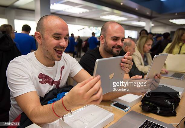 Customers Abraham Garcia left and George Vizziello both visiting from Spain check out the new Apple Inc iPad Air at the 5th Avenue Apple store in New...