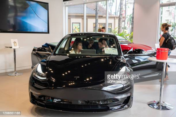 Customers admire a Tesla Model 3 electric vehicle at a Tesla store