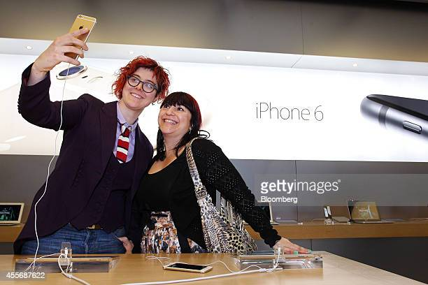 """Customers Alice Clarke, left, and Katie Cincotta take a """"selfie"""" photograph using an iPhone 6 Plus at the Apple Inc. George Street store during the..."""