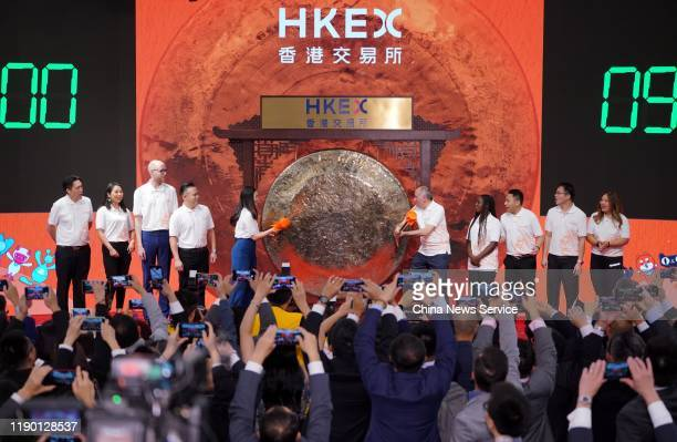 Customers and partners of Alibaba Group strike a gong during the company's listing ceremony at the Hong Kong Stock Exchange on November 26, 2019 in...