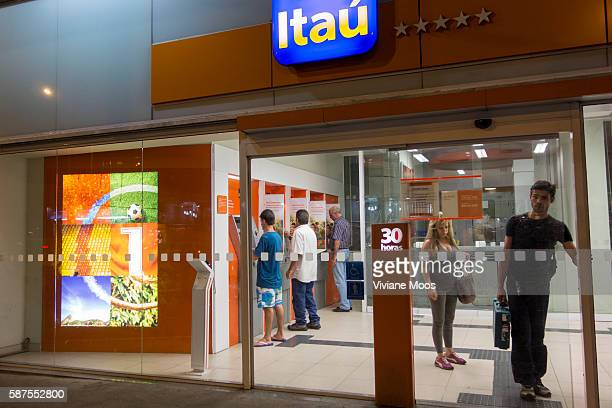 Customers and visitors using the cash machine ATM dispensers inside the secure lobby of Itau one of Brazil's major banks