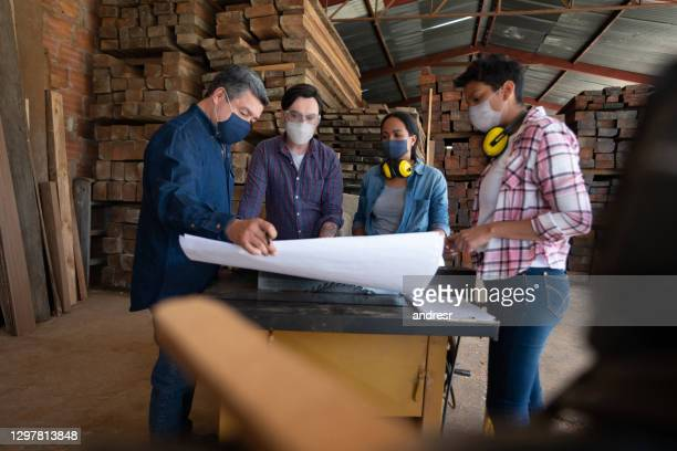 customers and workers at a furniture factory wearing facemasks while looking at the designs - biosecurity stock pictures, royalty-free photos & images