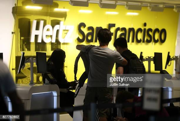 Customers are assisted at a Hertz rental car office on August 8 2017 in San Francisco California Rental car companies are seeing a drop in earnings...