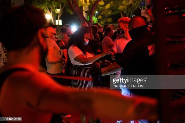 Customers are required by security to wear facemasks to enter a bar after midnight early Sunday morning on July 18, 2021 in West Hollywood,...