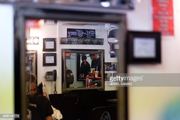 Customers are seen reflected in a mirror at a barber shop in Ferguson Missouri on November 22 2014 Tensions rose on November 22 in the troubled St...