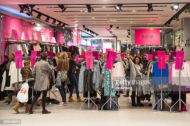 Customers are seen shopping for discounted clothing in a Topshop store operated by Arcadia Group PLC at the Westfield Stratford City mall during the...