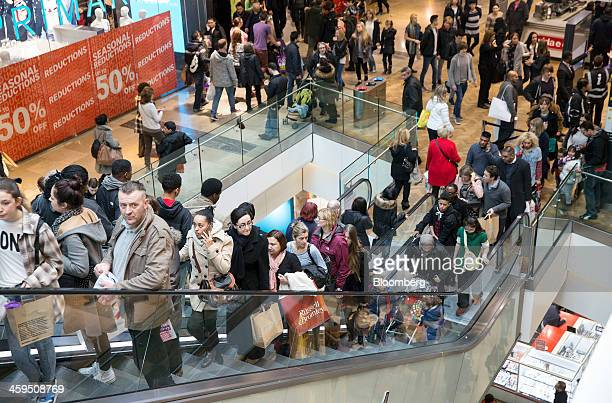 Customers are seen traveling on an escalator as they shop for discounted goods in the Christmas sales at the Westfield Stratford City mall in London...