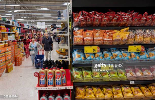 Customers are seen walking through the soft drink hallway at Carrefour supermarket in Spain