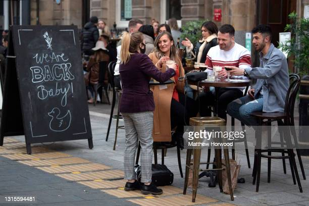 Customers are served while sat at tables outdoors on High Street on April 30, 2021 in Cardiff, Wales. Outdoor hospitality reopened on Monday in Wales...